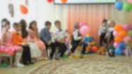 Children sit on chairs and look towards the hall Stock Footage