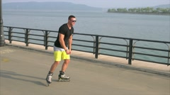 Young sporty man learns to roller skate on waterfront Stock Footage