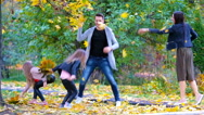Young family of four throwing leaves around on an autumn day outdoors Stock Footage