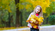Portrait of adorable little girl with yellow and orange leaves outdoors at Stock Footage