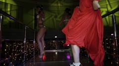 Girl in red dress, sneakers dance on stand on party in nightclub. Go go girls Stock Footage