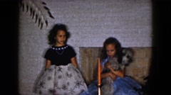 1961: two young girls pass a reluctant dog from one to the other/ MICHIGAN Stock Footage