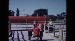 1961: two girls driving two mechanical toy tractors on structures with wood Stock Footage