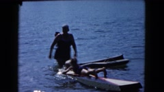 1961: mother watching over two children using flotation devices in the ocean Stock Footage
