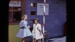 1961: two girls buy an entrance ticket at a ticket window and hand it to a blond Stock Footage
