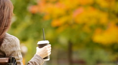 Fall concept - beautiful woman drinking coffee in autumn park under fall foliage Stock Footage
