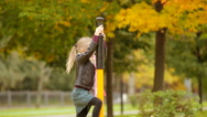 Little cute girl playing at the playground in autumn outdoors Stock Footage