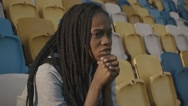 Young african american girl sitting on tribune and looking the match Stock Footage