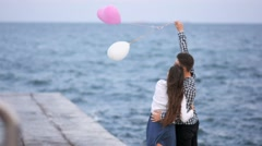 Young couple hugs and baloons fly awaynear the sea Stock Footage