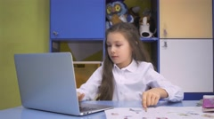 Girl using a laptop computer at school. Schoolgirl after lessons in library Stock Footage