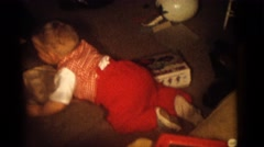 1964: happy child on floor surrounded by toys with man and two children by couch Stock Footage