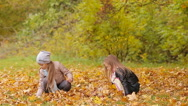 Little adorable girls having fun with leaves at warm day in autumn park outdoors Stock Footage