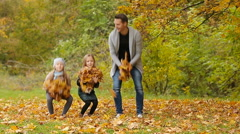 Young smiling family having fun and throwing leaves around on an autumn day Stock Footage