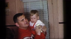 1964: father is holding his toddler son and cleaning his hand with a napkin Stock Footage