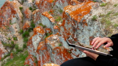 Girl's hands using a tablet PC on the rock, Olkhon Island, Lake Baikal Stock Footage