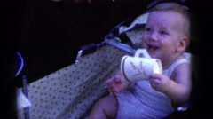 1964: happy baby boy plays with paper cup at young girl's birthday party CAMDEN Stock Footage