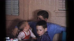 1964: a handsome young man in a blue sweater holding a baby in his lap CAMDEN Stock Footage