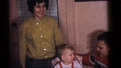 1964: toddler seated in front of a birthday cake and presented with a toy Stock Footage