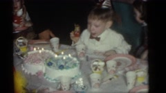 1964: a boy sitting at a table in front of a birthday cake with candles CAMDEN Stock Footage
