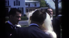 1964: a young man and woman get married in a yard beside a busy street  Stock Footage