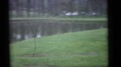 1964: a mother is holding her toddler boy at a lake  Stock Footage