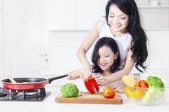 Cute girl and mother cutting paprika Stock Photos