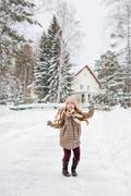 Girl in plaid winter coat dancing Stock Photos