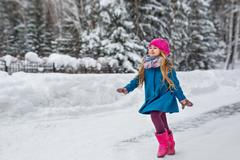 Cute six year old girl dressed in a blue coat and a pink hat and boots, fun r Stock Photos
