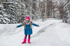Cute six year old girl dressed in a blue coat and a pink hat and boots, hammi Stock Photos