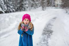 Cute little girl in a pink hat and blue coat freezing in winter Stock Photos