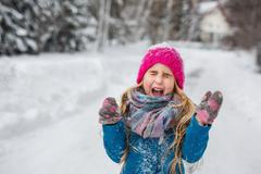 Little girl dressed in a blue coat and a pink hat joking screaming in the win Stock Photos