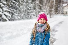 Little girl dressed in a blue coat and a pink cap closed her eyes Stock Photos