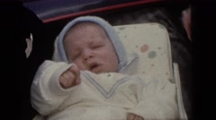 1964: father is holding his beautiful kid in his hand on a bed CAMDEN Stock Footage