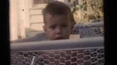1964: baby boy in diapers outdoor playing in a playpen in the yard CAMDEN Stock Footage