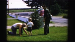 1956: young boy playing with older man working on lawn BOSTON Stock Footage