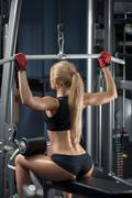 Brutal athletic woman doing back pullups at the gym Stock Photos