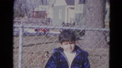 1963: a young boy in a coat standing in front of a chain-link fence LINCOLN Stock Footage