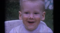 1964: blonde baby laughing with food on his face, surrounded by family  Stock Footage