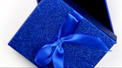 Rotating blue gift box on a paper background Stock Footage
