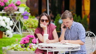 Young couple at outdoor cafe. Young girl is angry at her boyfriend because he is Stock Footage