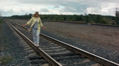 Girl walking on rail road bridge Stock Footage