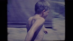 1968: two young boys playing in a muddy puddle outdoor COTTONWOOD, ARIZONA Stock Footage