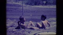 1968: two young boys playing in a muddy, water filled hole in the ground. Stock Footage