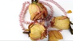 Rotating dried rose flowers with pink pearl necklace , selective focus. Stock Footage