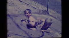 1968: two little boys playing in a self-made puddle. COTTONWOOD, ARIZONA Stock Footage