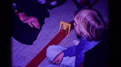 1968: an older man assists a child while assembling a train track  Stock Footage