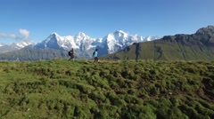 AERIAL SEQUENCE OF HIKERS WALKING WITH AMAZING SNOW CAP PEAKS Stock Footage