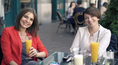 Portrait of two happy girlfriends sitting in cafe in the city, 4K Stock Footage