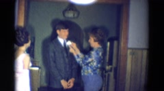1969: a mature woman pins a corsage to the suit of a young male  Stock Footage