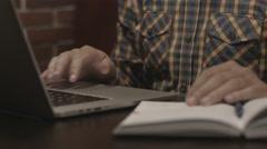 Man in plaid shirt working at laptop Stock Footage